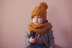 Kid in knitted mustard color hat