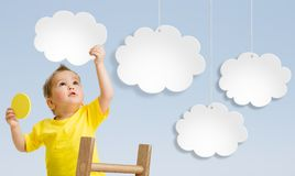 Kid with ladder attaching clouds to sky concept Stock Photos