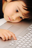 Kid and laptop Stock Images