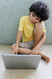 Kid with laptop. A child sitting on the floor and working on his laptop Stock Photo