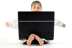 Kid with laptop. A genius little boy using a laptop kept on his lap, isolated on a white background Stock Photos