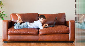 Kid with a laptop on the couch Stock Photo