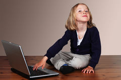 Kid on laptop playing Stock Photo