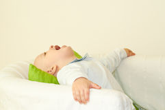 Kid laughing. Young boy laughing on a white armchair with a green pillow Stock Photography