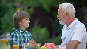 Kid laughing with grandpa telling funny stories, family having fun together