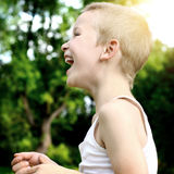 Kid Laughing. Side view of the Happy Kid Laughing outdoor Stock Photos
