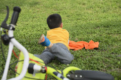 Kid on lawn with bicycle Stock Images