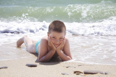 Kid laying on beach Royalty Free Stock Images