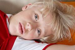 Kid laying down wearing soccer team tshirt. Royalty Free Stock Image