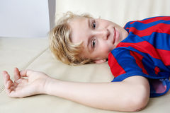 Kid laying down wearing soccer team tshirt. Royalty Free Stock Photo