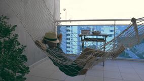 Kid laying and relaxing in hammock hanging on balcony of apartment. Kid swinging and dreaming, thinking