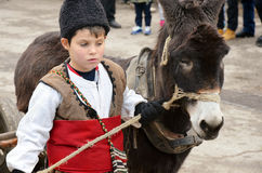 Kid leading donkey. Young kid leading a donkey and wearing traditional bulgarian costume at yearly masquerade festival in Pernik, Bulgaria. The event happens stock photo