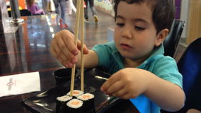 Kid learn to eat with chopsticks stock footage