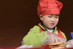 Kid making hamburger Royalty Free Stock Image