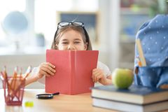 Kid is learning in class. Back to school! Happy cute industrious child is sitting at a desk indoors. Kid is learning in class stock photo