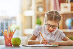 Kid is learning in class. Back to school! Happy cute industrious child is sitting at a desk indoors. Kid is learning in class royalty free stock images
