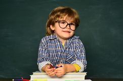 Kid is learning in class on background of blackboard. Little children at school lesson. Home schooling.  stock photo