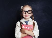 Kid learning french in language school. Happy little girl. Holding book in her hands on blackboard royalty free stock photos
