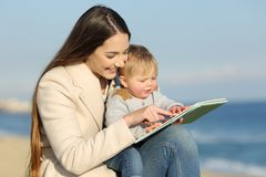 Kid learning and mother showing a book Royalty Free Stock Photo