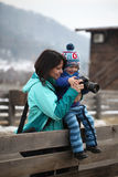 Kid learning photography. A smiling kid is learning how to take a photo from his mother Royalty Free Stock Image