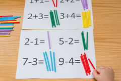 Kid learning simple subtraction and addition by counting sticks Royalty Free Stock Images