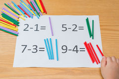 Kid learning simple subtraction. By counting numbers of sticks Stock Images