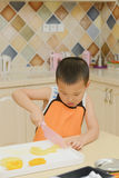 Kid learning to cook Stock Images