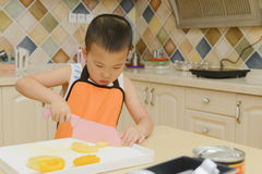 Kid learning to cook Stock Photos