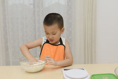 Kid learning to cook Stock Photography