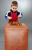 Kid learning to play chess Stock Image