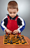 Kid learning to play chess Stock Photos