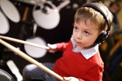Kid learning to play drums stock images