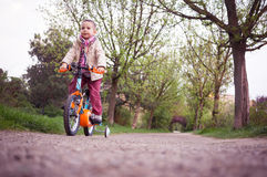 Kid learning to ride the bicycle in the park Royalty Free Stock Image