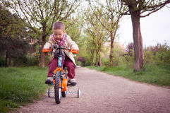 Kid learning to ride the bicycle in the park Royalty Free Stock Photos
