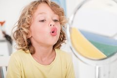 Kid learning to speak in front of a mirror during correct pronun royalty free stock image