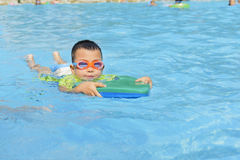 Kid learning to swim in summer. Chinese kid learning to swim in pool at summer day royalty free stock image