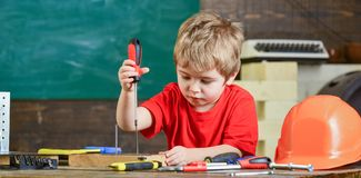 Kid learning to use screwdriver. Concentrated kid working in repairs workshop. Future occupation concept.  royalty free stock photo
