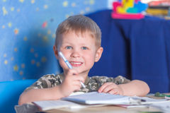 Kid learning to write. Preschool smiling boy learning to write literacy Stock Photography