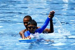 A kid learns how to swim with the help of a swimming coach. Stock Photos