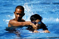 A kid learns how to swim with the help of a swimming coach. stock photography