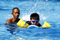 A kid learns how to swim with the help of a swimming coach. royalty free stock photos