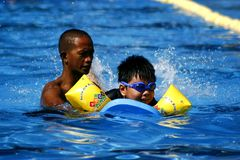 A kid learns how to swim with the help of a swimming coach. royalty free stock image