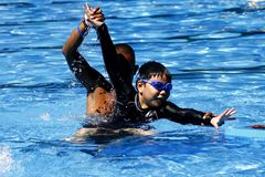 A kid learns how to swim with the help of a swimming coach. stock photo