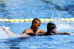 A kid learns how to swim with the help of a swimming coach. royalty free stock photography