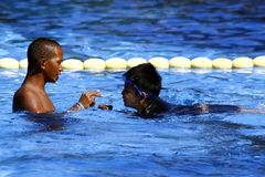 A kid learns how to swim with the help of a swimming coach. stock images