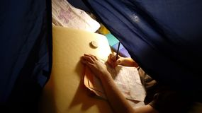 A kid learns in a tent. Writing hand. Child, kid, homeschooler learns writes studies in a tent at home or traveling, writing hand stock images