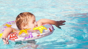 Kid learns to swim using a plastic water ring. In the swimming pool or waterpark stock footage