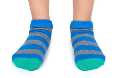 Kid legs in striped socks isolated on white background.  Royalty Free Stock Photos