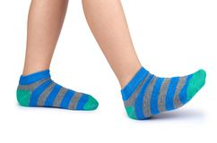 Kid legs in striped socks isolated on white background.  Stock Photo