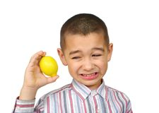 Kid with lemon. Six-year-old boy holding a lemon and making a sour face, isolated on white background Stock Photo